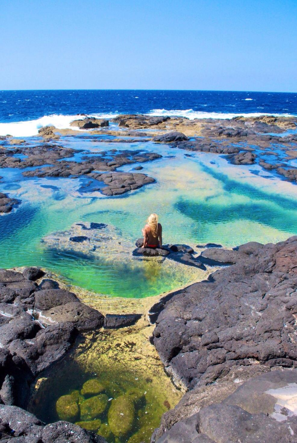 woman with blonde hair sat relaxing in the natural pools of Los Charcones